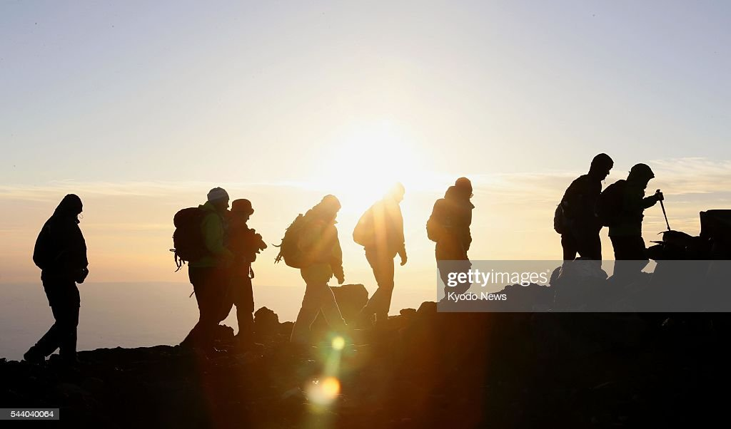 Climbers approach the top of Mt. Fuji in sunlight at 4:55 a.m. on July 1, 2016, the first day of the climbing season for the 3,776-meter mountain. Straddling Shizuoka and Yamanashi prefectures in central Japan, Mt. Fuji is designated a UNESCO World Heritage site.