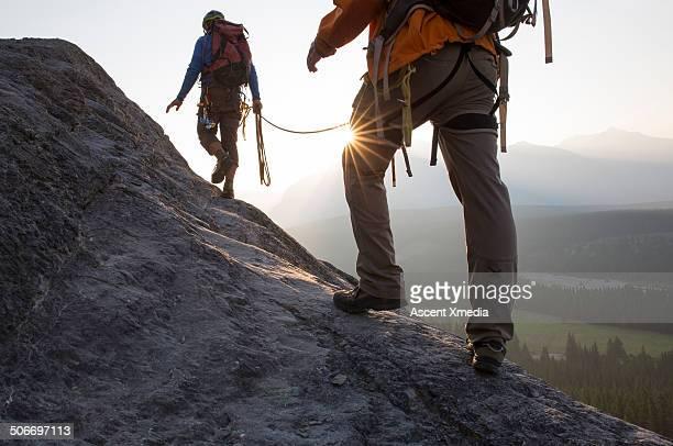 Climbers ascend mountain ridge, sunrise