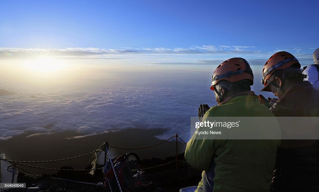 Climbers atop Mt. Fuji put their hands together as they face toward the sunrise at 4:42 a.m. on July 1, 2016, the first day of the climbing season for the 3,776-meter mountain. Straddling Shizuoka and Yamanashi prefectures in central Japan, Mt. Fuji is designated a UNESCO World Heritage site.