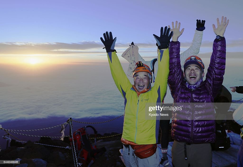 Climbers celebrate at the top of Mt. Fuji as the sun rises at 4:34 a.m. on July 1, 2016, the first day of the climbing season for the 3,776-meter mountain. Straddling Shizuoka and Yamanashi prefectures in central Japan, Mt. Fuji is designated a UNESCO World Heritage site.