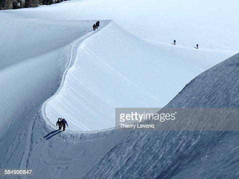 Climbers going up a snow ridge