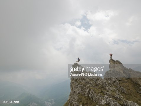 Climbers hold hands outstretched, pinnacle summit : Stock Photo