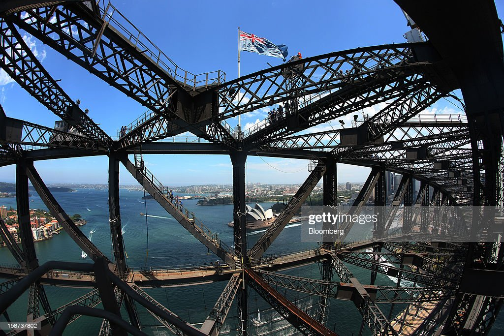 Climbers make their way towards the summit as they scale the Sydney Harbour Bridge during a guided tour operated by BridgeClimb in this photograph taken with a fish-eye lens in Sydney, Australia, on Monday, Dec. 24, 2012. Beginning next month, people wanting to ascend 134 meters above sea level to the top of the bridge spanning Sydney Harbour will have the option to hear guides speak Mandarin. Photographer: Brendon Thorne/Bloomberg via Getty Images