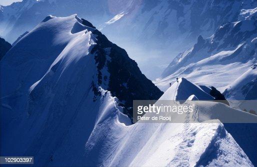 Climbers on a long icy ridge