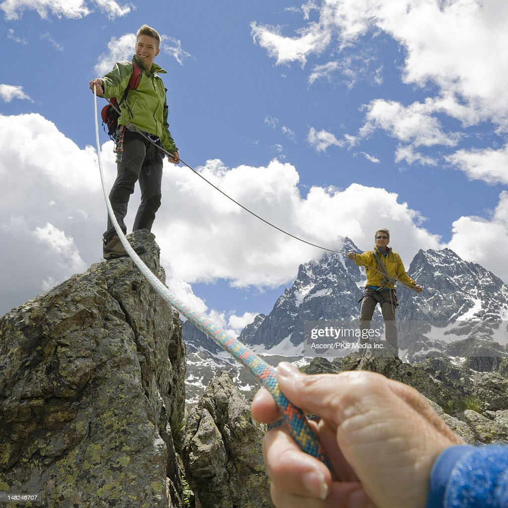 Climbers on ridge pull rope tight to teammate : Stock Photo