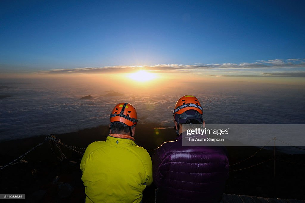 Climbers pose with the first sunrise of the climbing season at the summit of Mount Fuji on July 1, 2016 in Japan. Mount Fuji climbing season runs through September 10.