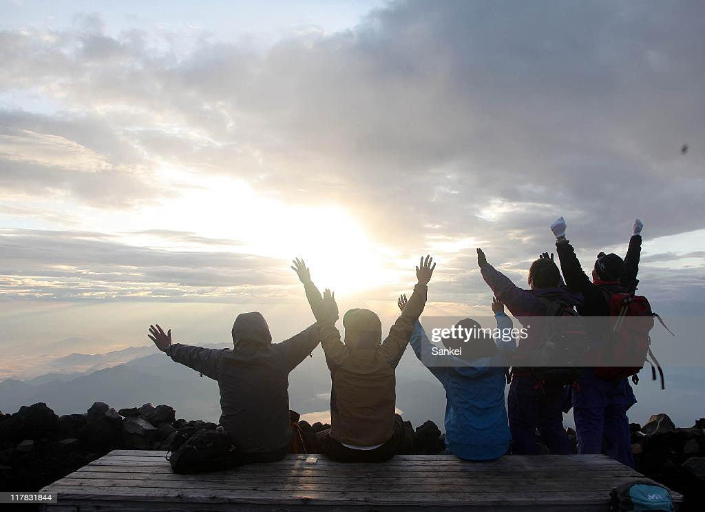 Climbers raise Banzai cheers to the sunrize on the summit of Mount Fuji on July 1, 2011 in Fujiyoshida, Yamanashi, Japan.