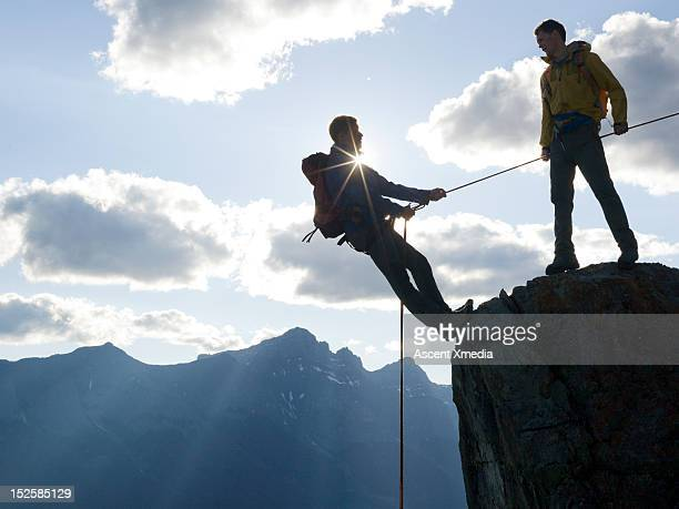 Climbers rappel (abseil) from cliff, mtns below