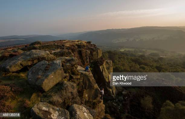 Climbers scale the Millstone Quarry at sunset in the Peak District on September 09 2014 in Hathersage United Kingdom Much of the UK continues to...