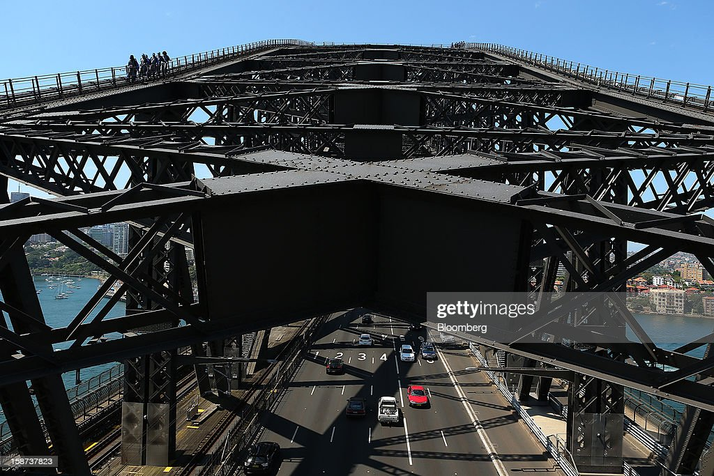 Climbers scale the Sydney Harbour Bridge during a guided tour operated by BridgeClimb as traffic moves below in Sydney, Australia, on Monday, Dec. 24, 2012. Beginning next month, people wanting to ascend 134 meters above sea level to the top of the bridge spanning Sydney Harbour will have the option to hear guides speak Mandarin. Photographer: Brendon Thorne/Bloomberg via Getty Images