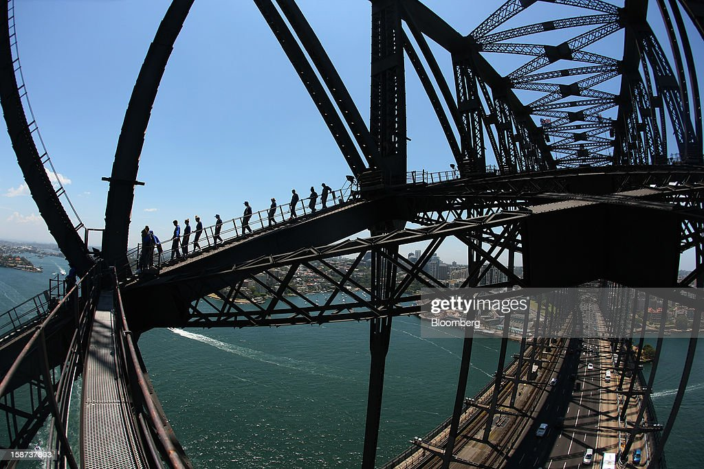 Climbers scale the Sydney Harbour Bridge during a guided tour operated by BridgeClimb in this photograph taken with a fish-eye lens in Sydney, Australia, on Monday, Dec. 24, 2012. Beginning next month, people wanting to ascend 134 meters above sea level to the top of the bridge spanning Sydney Harbour will have the option to hear guides speak Mandarin. Photographer: Brendon Thorne/Bloomberg via Getty Images