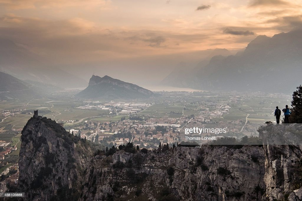 Climbers stand at the mountain Colodri and look toward Arco and the Lake Garda on October 27 2014 in Arco Italy The mountains around Arco are a Mecca...
