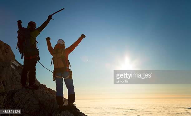 Climbers standing on rock and celebrating