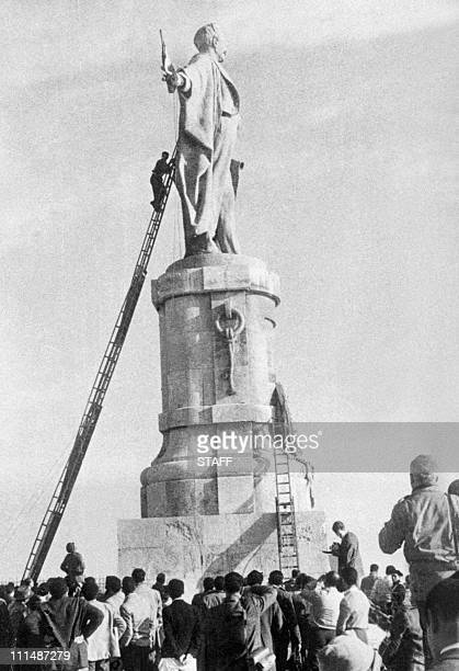 climbing a scale an Egyptian tries to reach French flag in the hand of Ferdinand de Lesseps statue to burn it 30 December 1956 two days after French...
