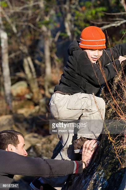 Klettern Junge mit Hilfe von Vater