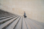 Profile shot of a businessman walking stairs up to work in the city of Paris.