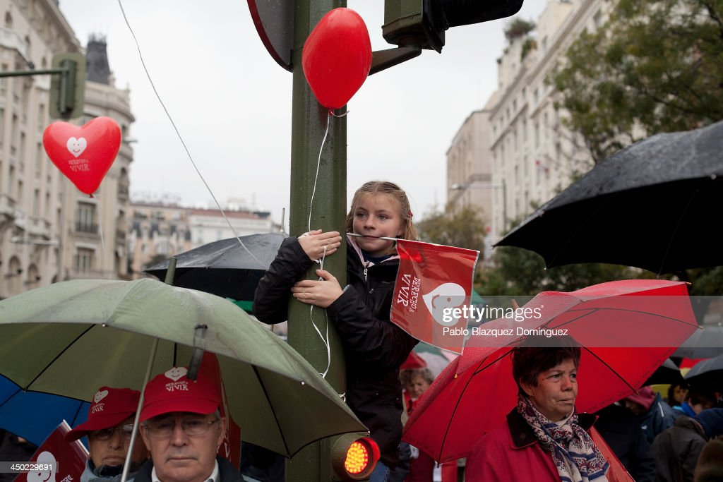 A clings onto traffic lights while holding a flag printed with the slogan 'Right To Live' ('Derecho A Vivir') during a Pro-Life demonstration against abortion on November 17, 2013 in Madrid, Spain.