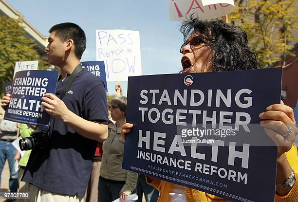 Clinic workers hold signs and chant during a rally in support of US President Barack Obama's health care reform package March 17 2010 in Oakland...