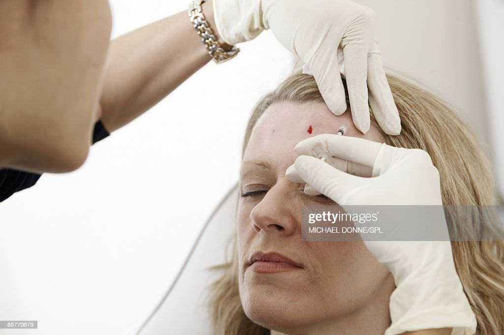 Clinician injecting Botox into female patient : Stock Photo