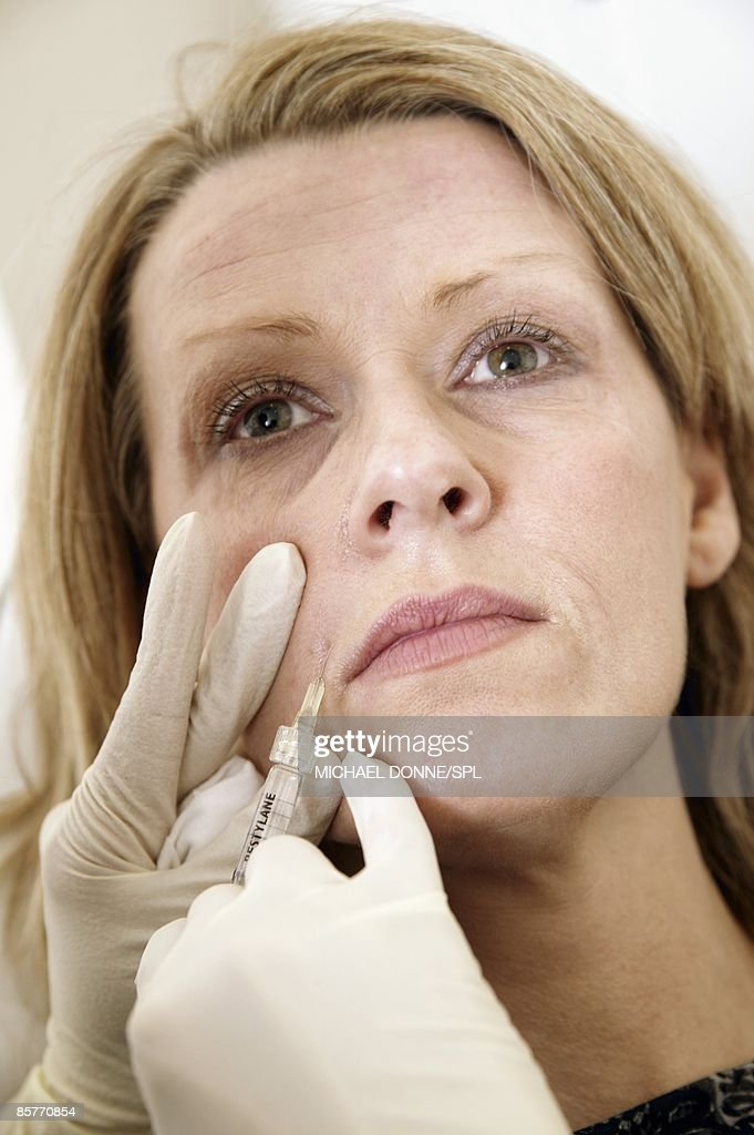 Clinician injecting female patient : Stock Photo