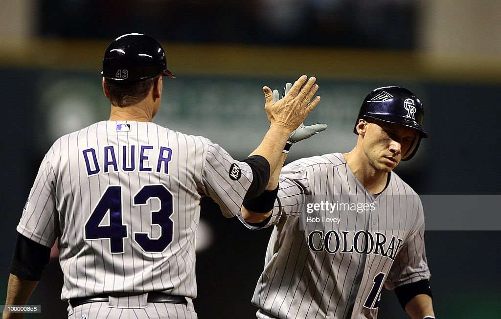 Clint Barmes #12 of the Colorado Rockies receives a high five from third base coach Rich Dauer #43 after hitting a home run in the seventh inning against the Houston Astros at Minute Maid Park on May 19, 2010 in Houston, Texas.