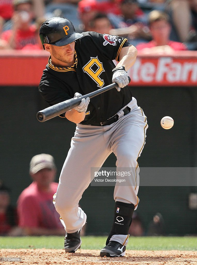 <a gi-track='captionPersonalityLinkClicked' href=/galleries/search?phrase=Clint+Barmes&family=editorial&specificpeople=208223 ng-click='$event.stopPropagation()'>Clint Barmes</a> #12 of the Pittsburgh Pirates lays down a sacrifice bunt to advance Pedro Alvarez #24 (not in photo) to third base in the tenth inning during the MLB game against the Los Angeles Angels of Anaheim at Angel Stadium of Anaheim on June 23, 2013 in Anaheim, California. The Pirates defeated the Angels 10-9 in ten innings.