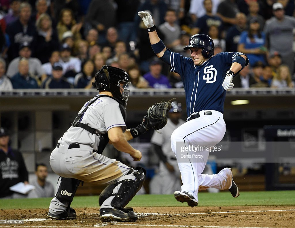 Clint Barmes #12 of the San Diego Padres scores ahead the throw to Nick Hundley #4 of the Colorado Rockies during the sixth inning of a baseball at Petco Park May 2, 2015 in San Diego, California.