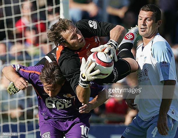 Clint Bolton of Sydney makes a save over the top of Bobby Despotovski of the Glory during the round 20 ALeague match between Perth Glory and Sydney...