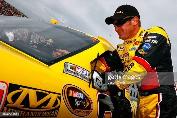 Clint Bowyer dirver of the Cheerios / Hamburger Helper Chevrolet reachs into his car on the grid prior to the start of the NASCAR Sprint Cup Series...