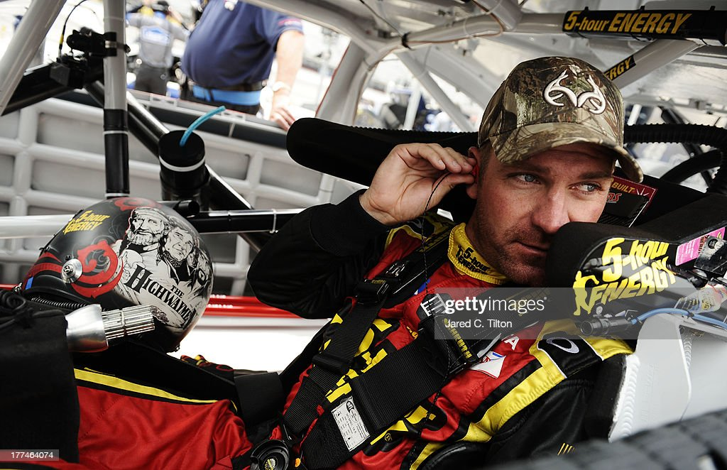 Clint Bowyer, driver of the #15 5-hour ENERGY Toyota, adjusts his equipment in his car during practice for the NASCAR Sprint Cup Series IRWIN Tools Night Race at Bristol Motor Speedway on August 23, 2013 in Bristol, Tennessee.