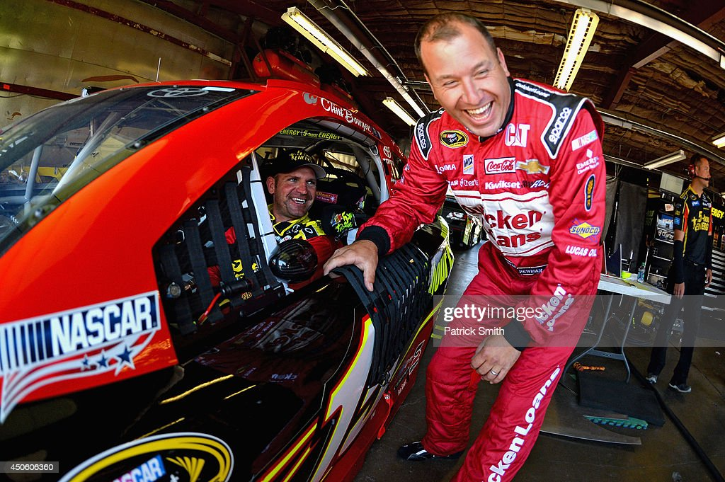 Clint Bowyer, driver of the #15 5-hour ENERGY Toyota, and Ryan Newman, driver of the #31 Quicken Loans Chevrolet, talk in the garage area during practice for the NASCAR Sprint Cup Series Quicken Loans 400 at Michigan International Speedway on June 14, 2014 in Brooklyn, Michigan.
