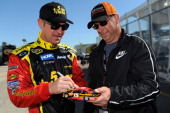 Clint Bowyer driver of the 5hour ENERGY Toyota signs an autograph during qualifying for the NASCAR Sprint Cup Series Daytona 500 at Daytona...