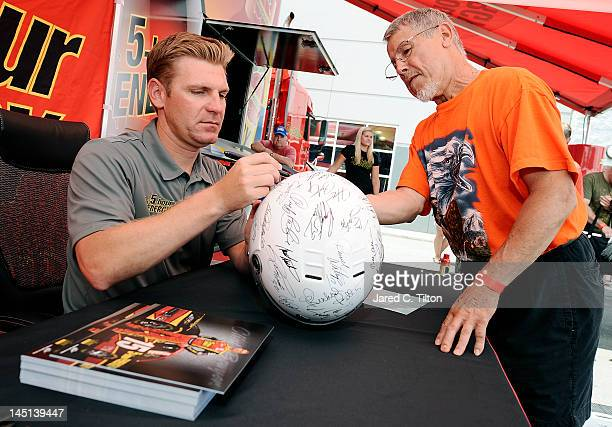 Clint Bowyer driver of the 5hour Energy Toyota signs autographs for fans during Michael Waltrip Racing hosts fan day on May 23 2012 in Davidson North...