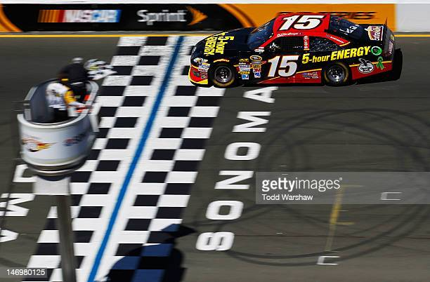 Clint Bowyer driver of the 5hour Energy Toyota takes the checkered flag as he crosses the finish line to win the NASCAR Sprint Cup Series Toyota/Save...