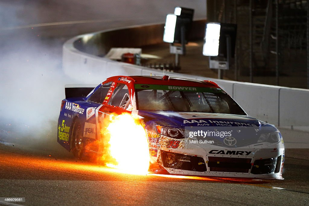 Clint Bowyer driver of the AAA Insurance Toyota heads to pit row while on fire during the NASCAR Sprint Cup Series Toyota Owners 400 at Richmond...