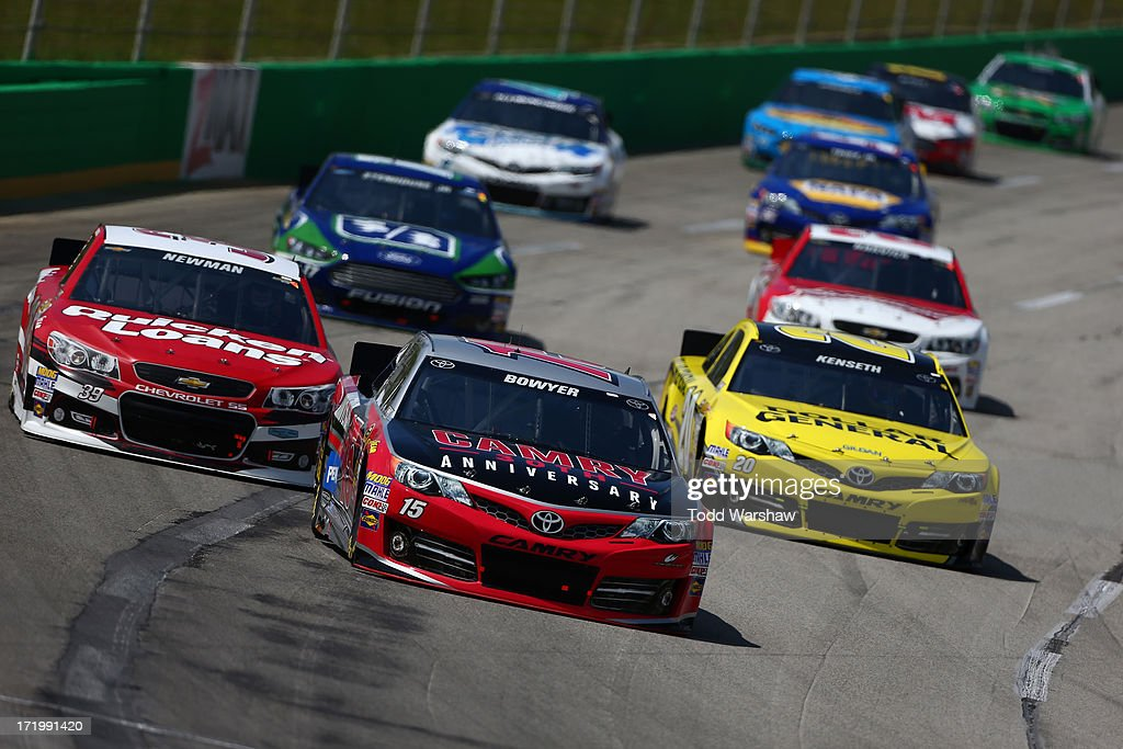 Clint Bowyer, driver of the #15 Camry 30th Anniversary Toyota, leads a group of cars during the NASCAR Sprint Cup Series Quaker State 400 at Kentucky Speedway on June 30, 2013 in Sparta, Kentucky.