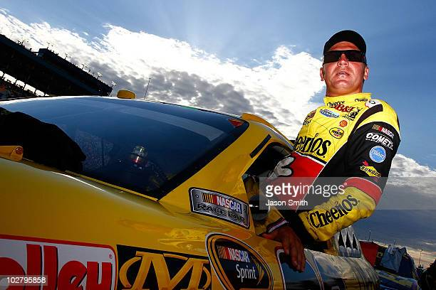 Clint Bowyer driver of the Cheerios / Hamburger Helper Chevrolet climbs into the car during the NASCAR Sprint Cup Series LIFELOCKCOM 400 at the...