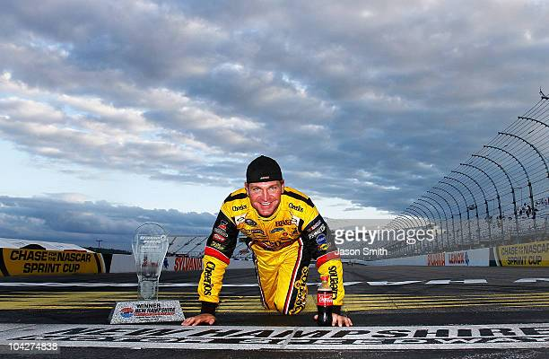 Clint Bowyer driver of the Cheerios / Hamburger Helper Chevrolet poses at the start/finish line after he won the NASCAR Sprint Cup Series Sylvania...