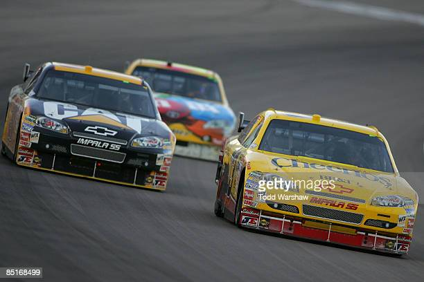 Clint Bowyer driver of the Cheerios/Hamburger Helper Chevrolet and Jeff Burton driver of the Caterpillar Chevrolet drive during the NASCAR Sprint Cup...