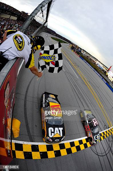 Clint Bowyer driver of the Chevy 100 Years Chevrolet leads Jeff Burton driver of the Caterpillar Chevrolet across the finish line to win the NASCAR...