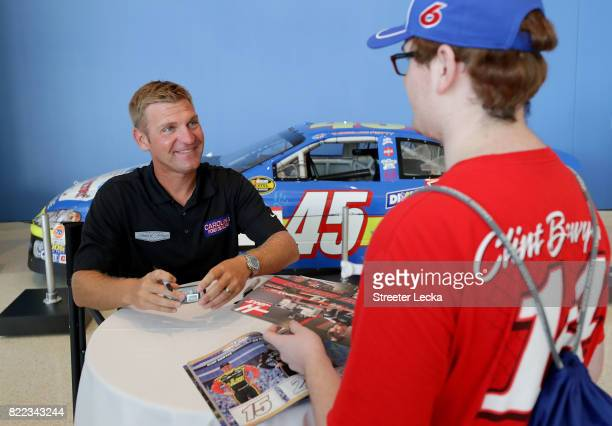 Clint Bowyer driver of the Ford Fusion for StewartHaas Racing signs autographs during the Darlington Throwback Paint Scheme Unveil at NASCAR Hall of...