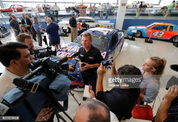 Clint Bowyer driver of the Ford Fusion for StewartHaas Racing speaks to the media in front of the race car during the Darlington Throwback Paint...