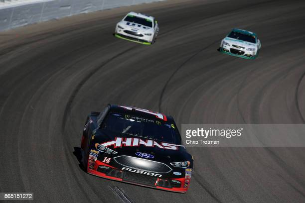 Clint Bowyer driver of the Haas Automation Ford leads Brad Keselowski driver of the Miller Lite Ford and Kasey Kahne driver of the UniFirst Chevrolet...