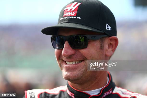 Clint Bowyer driver of the Haas Automation Ford looks on prior to the Monster Energy NASCAR Cup Series Hollywood Casino 400 at Kansas Speedway on...