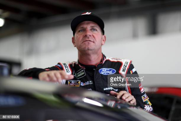 Clint Bowyer driver of the Haas Automation Ford stands in the garage area during practice for the Monster Energy NASCAR Cup Series ISM Connect 300 at...