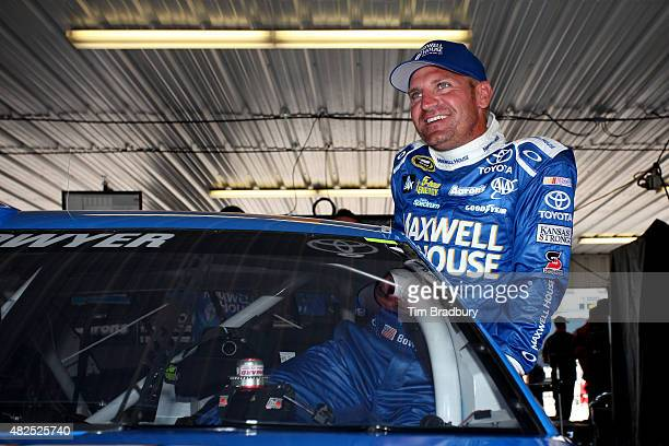 Clint Bowyer driver of the Maxwell House Toyota gets in his car in the garage during practice for the NASCAR Sprint Cup Series Windows 10 400 at...