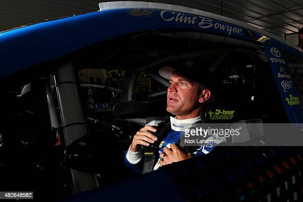 Clint Bowyer driver of the Maxwell House Toyota sits in his car in the garage during practice for the NASCAR Sprint Cup Series Windows 10 400 at...