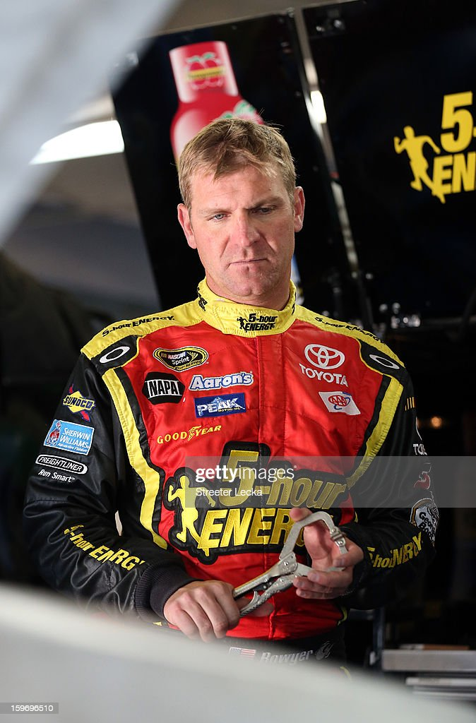 Clint Bowyer, driver of the #15 Michael Waltrip Racing Toyota, looks at the engine in his car during NASCAR Testing at Charlotte Motor Speedway on January 18, 2013 in Charlotte, North Carolina.