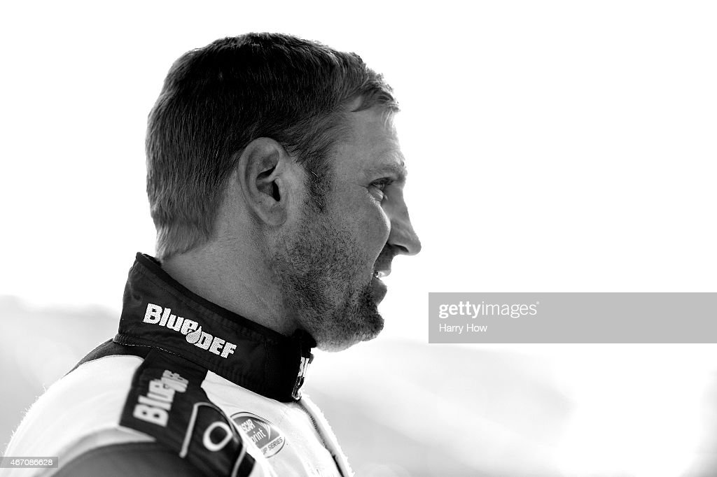 Clint Bowyer driver of the PEAK BluDEF Toyota stands on the grid during qualifying for the NASCAR Sprint Cup Series Auto Club 400 at Auto Club...