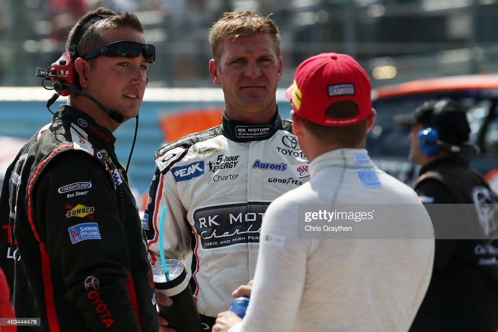 Clint Bowyer, driver of the #15 RK Motors Charlotte Toyota, center, talks with Jamie McMurray, driver of the #1 McDonald's Chevrolet, right, in the pits during a red-flag for an on-track incident during the NASCAR Sprint Cup Series Cheez-It 355 at Watkins Glen International on August 10, 2014 in Watkins Glen, New York.